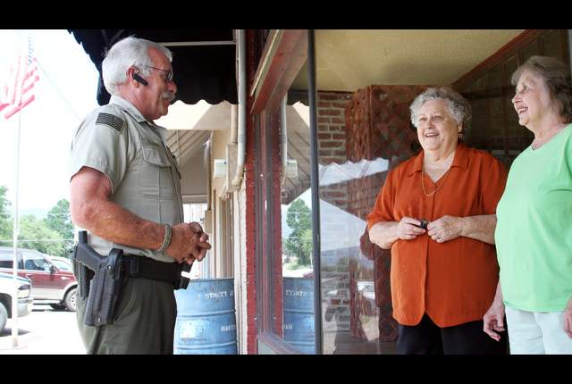 Cpl. Bill Cooper is seen here talking to residents in Hartford (AR). Photo Courtesy, SW Times.