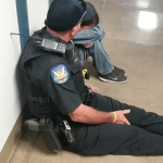 Police Officer Sits On Floor, Comforts Crying Student